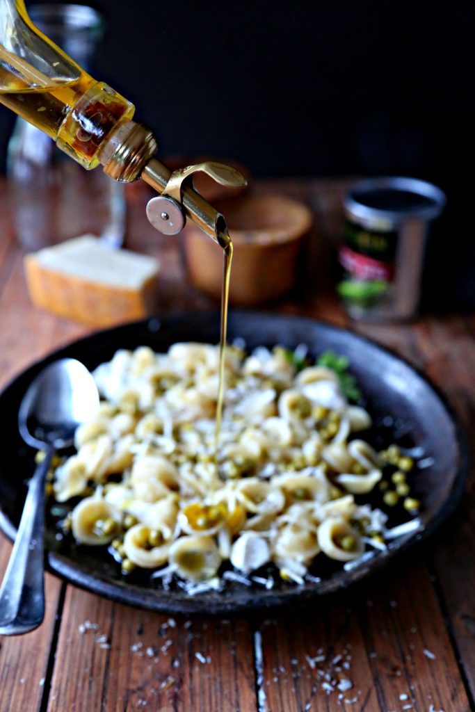 brown plate of orecchiette pasta with peas and parmesan with bottle of olive oil being drizzle on top