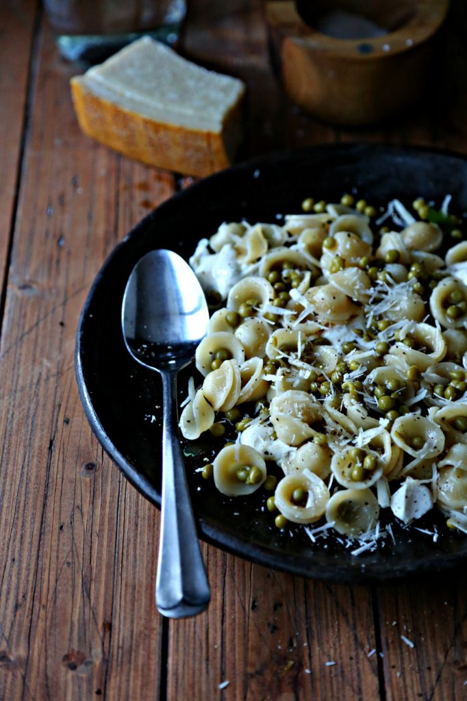 brown plate with silver spoon filled with orecchiette pasta with peas and parmesan.