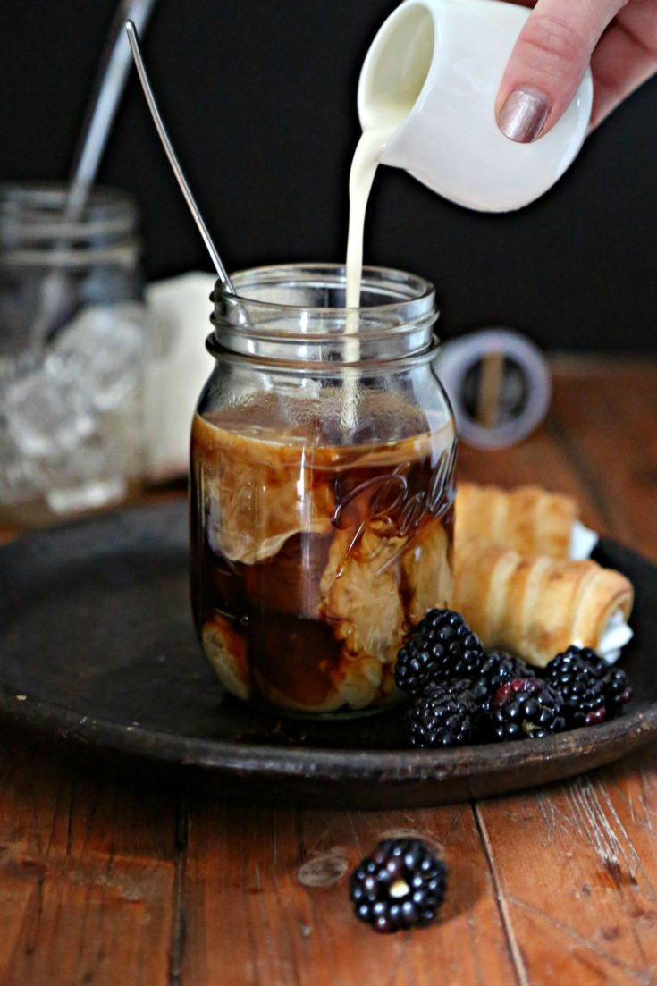 cream pouring into coffee over ice on dark plate with berries and pastry