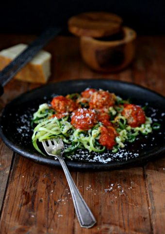 zucchini noodles and meatballs on a brown plate with fork