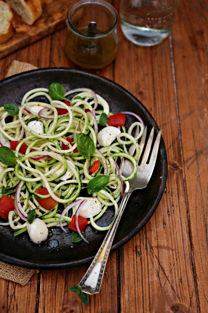 zucchini noodle salad on brown plate with silver serving fork