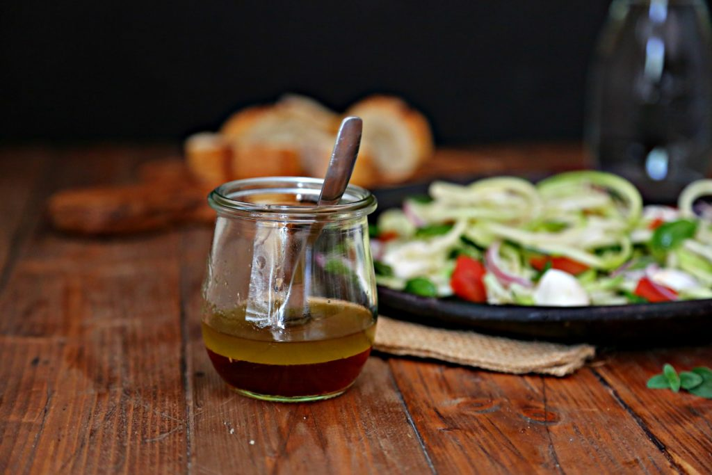 jar of vinaigrette with zucchini noodle salad on plate behind