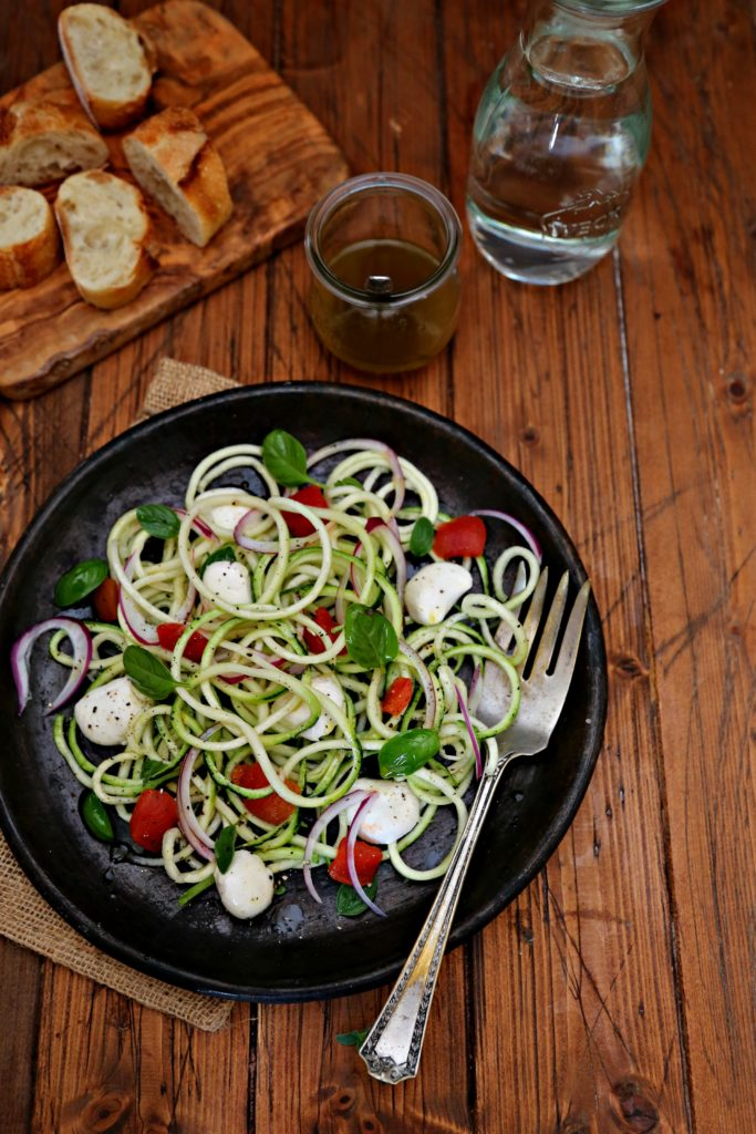 zucchini noodle salad on brown plate with silver fork, jar of vinaigrette on side with a board of bread slices