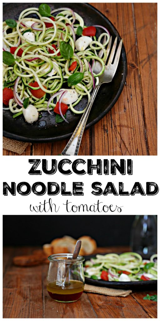 Zucchini noodle salad with tomatoes on plate with silver fork, jar of vinaigrette