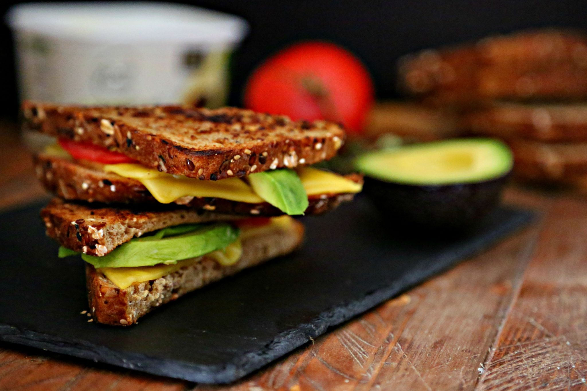 Avocado and Tomato Vegan Grilled Cheese on slate with tomato, butter and avocado surrounding.