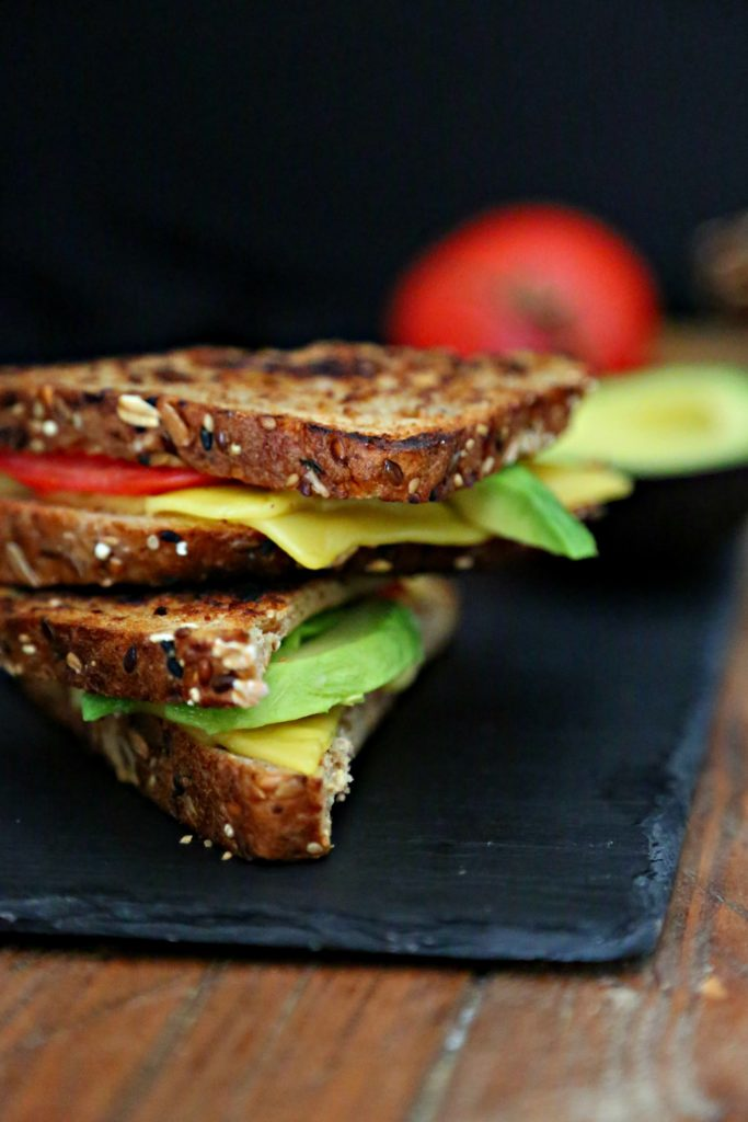 Avocado and Tomato Vegan Grilled Cheese on slate with tomato and avocado surrounding