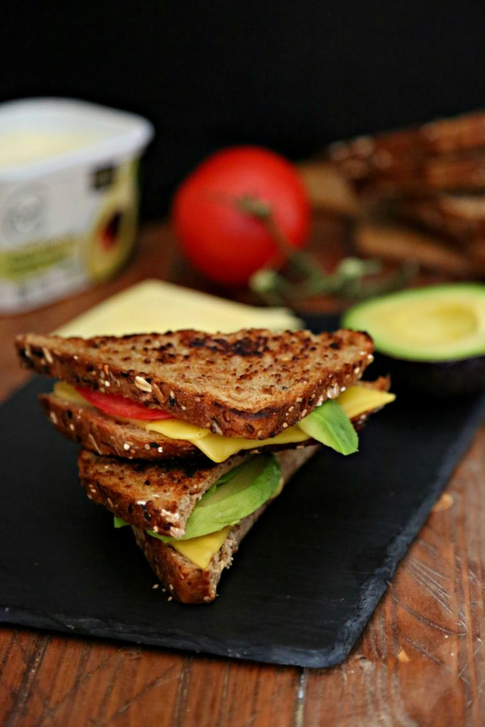 Avocado and Tomato Vegan Grilled Cheese on slate with tomato, butter and butter in background