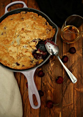 Cherry Cobbler in lavender skillet with spoon.