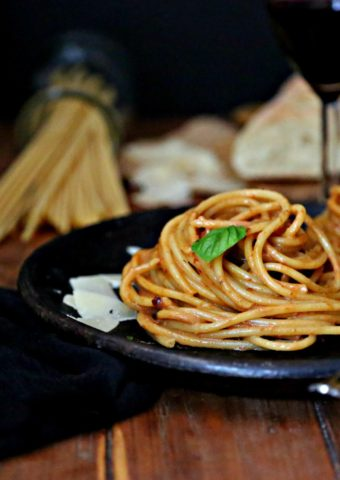 Bucatini with Creamy Sun Dried Tomato Sauce on brown plate surrounded by bread and a jar with uncooked bucatini