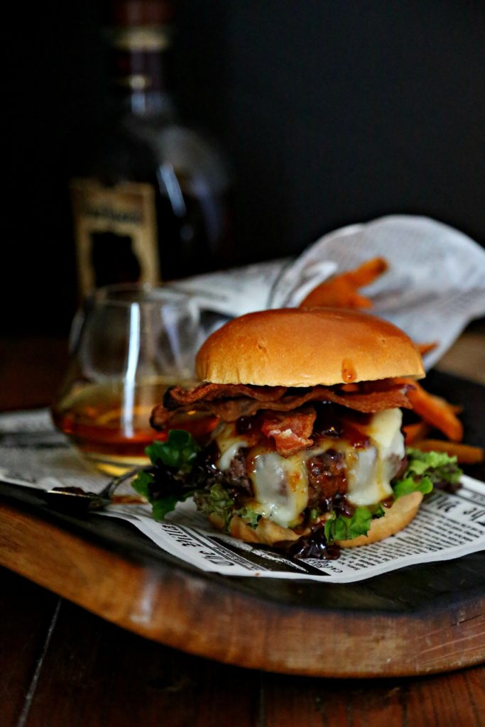 Bacon Brie Brioche Burger on cutting board with whiskehy glass and sweet potato fries