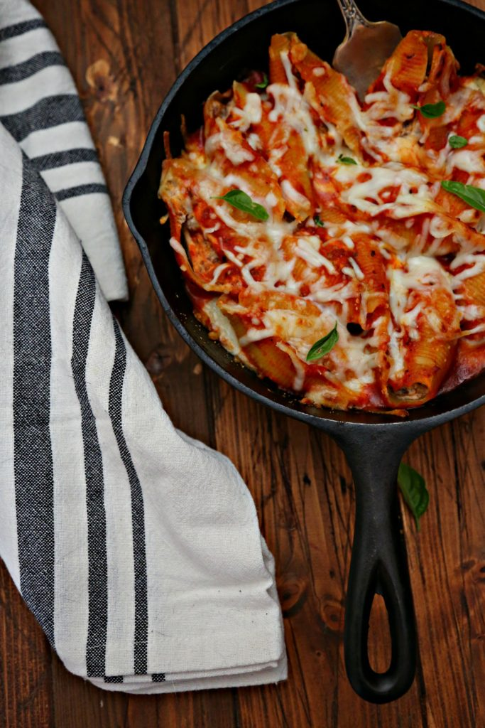 Skillet of Bolognese Stuffed Shells with kitchen towel
