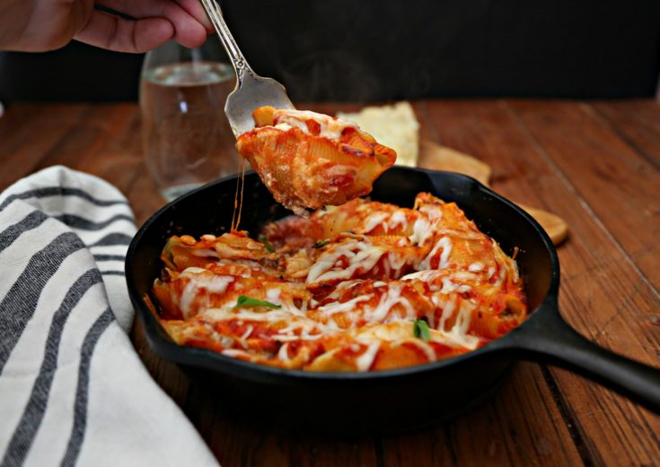 Bolognese Stuffed Shells in skillet, serving fork lifting one shell out. Carafe of water behind skillet.