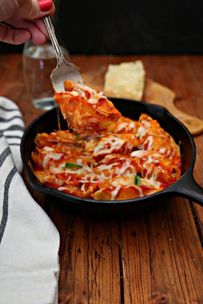 Bolognese Stuffed Shells in skillet with fork pulling one out