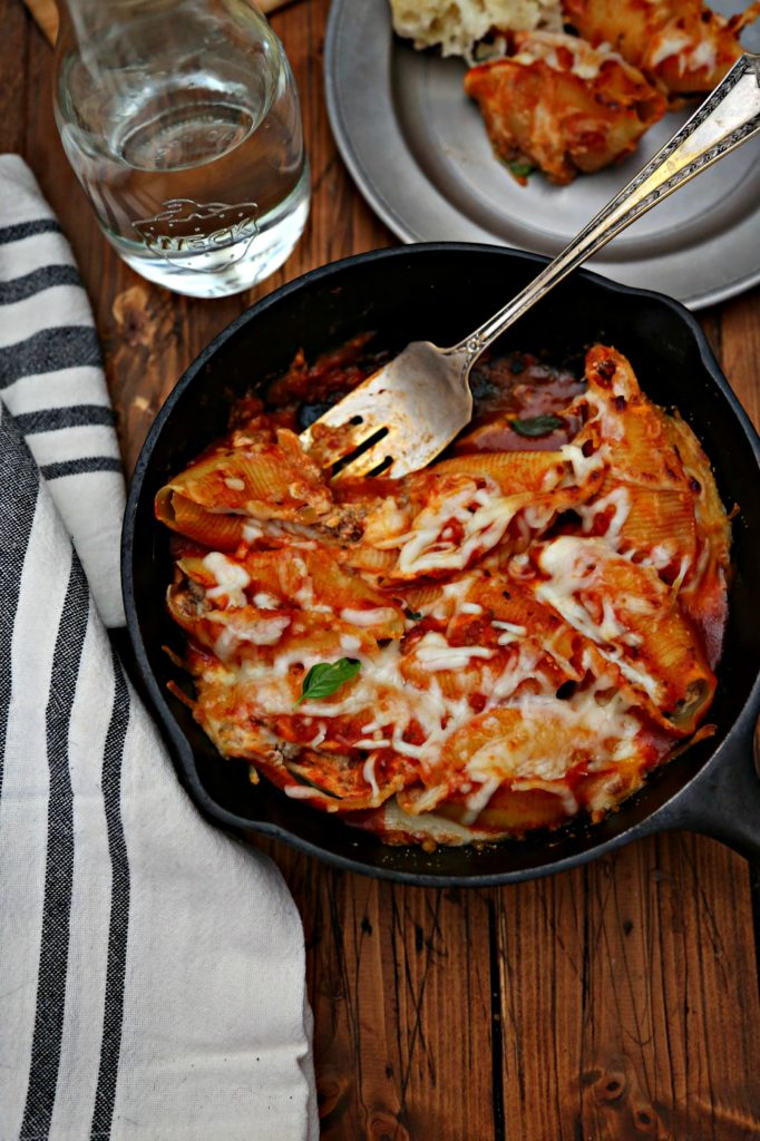 Bolognese Stuffed Shells in skillet with serving fork and some missing