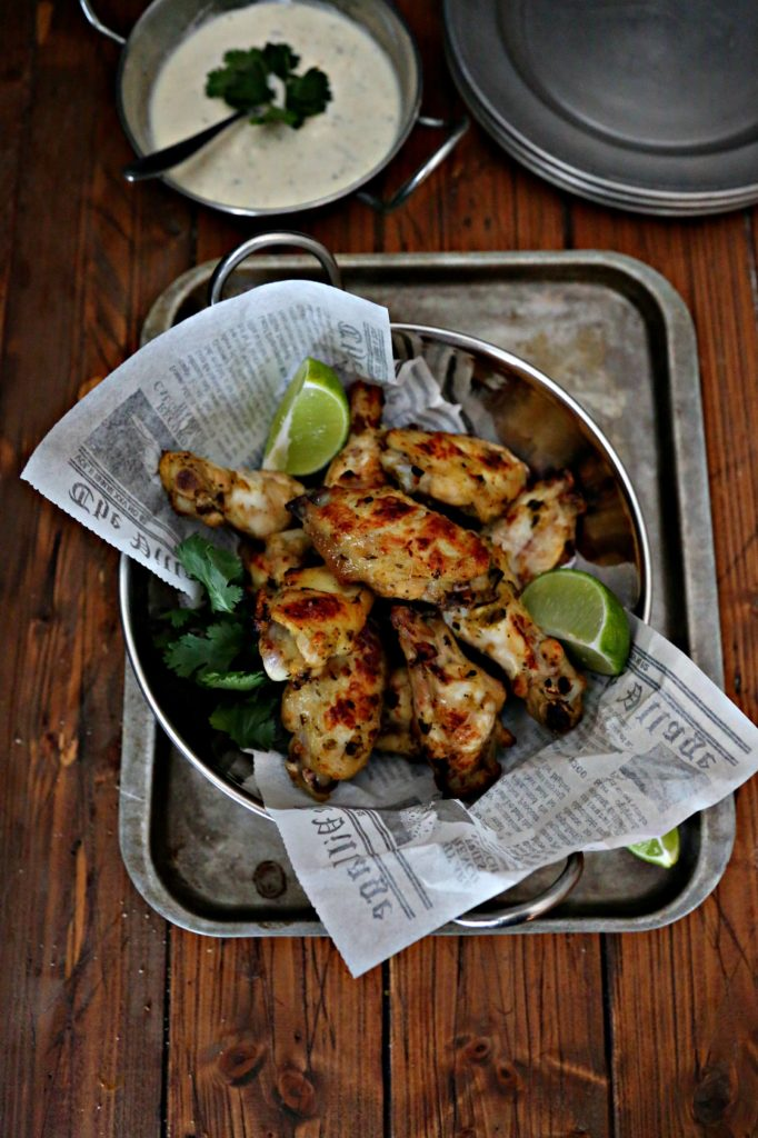 Glazed Salsa Verde Chicken Wings in a silver bowl sitting on a baking tray
