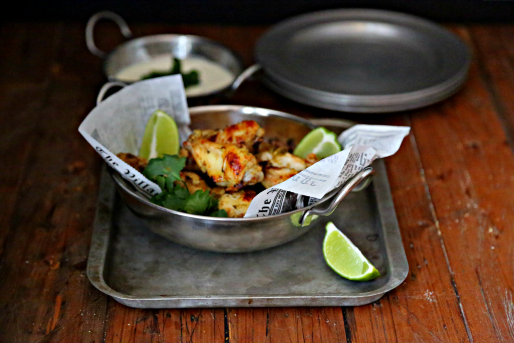 Glazed Salsa Verde Chicken Wings in silver bowl with limes on baking sheet with dipping sauce behind
