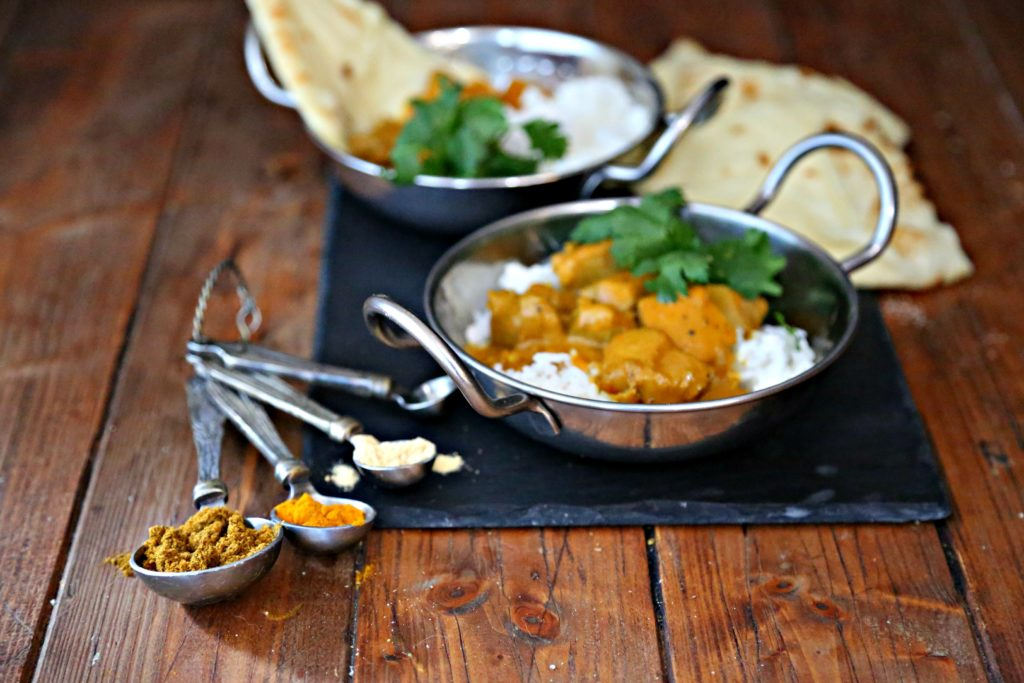 two bowls of easy Indian butter chicken with rice and naan. Measuring spoons filled with Indian spices.
