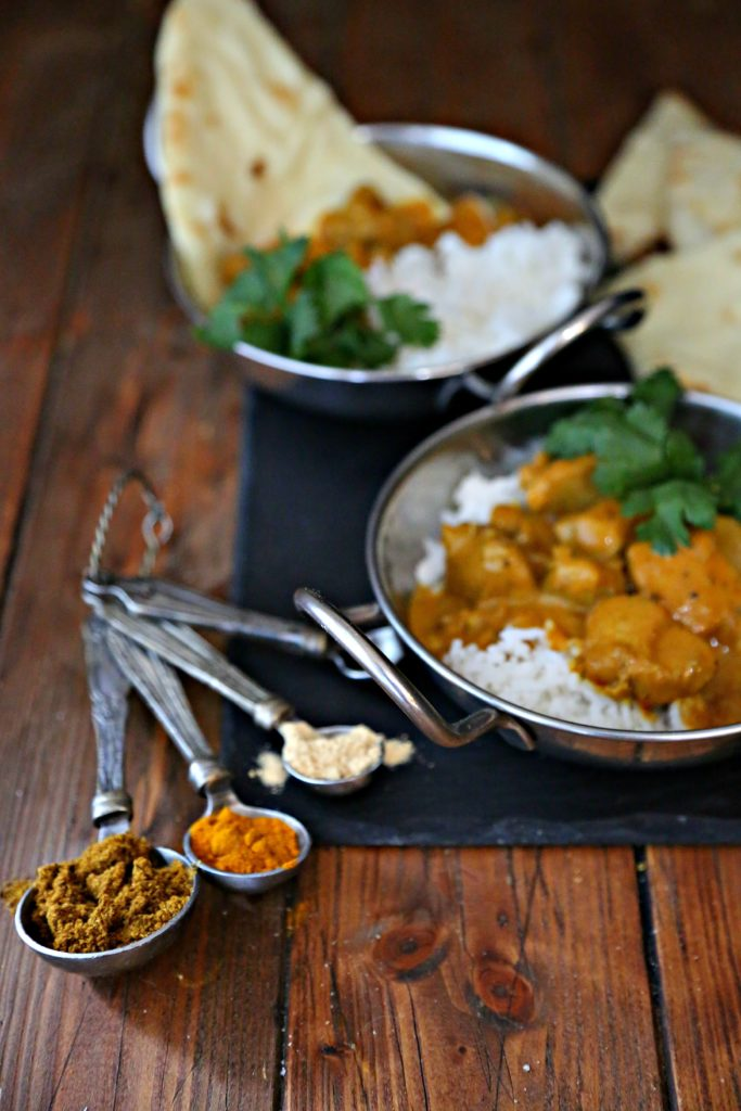 2 bowls of easy Indian butter chicken with rice and naan bread. Measuring spoons filled with Indian spices.