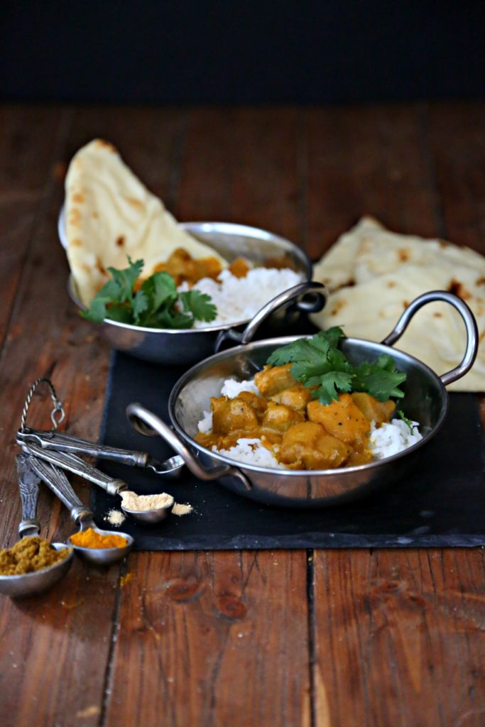 2 bowls of easy Indian butter chicken with rice and naan bread. Measuring spoons with Indian spices.