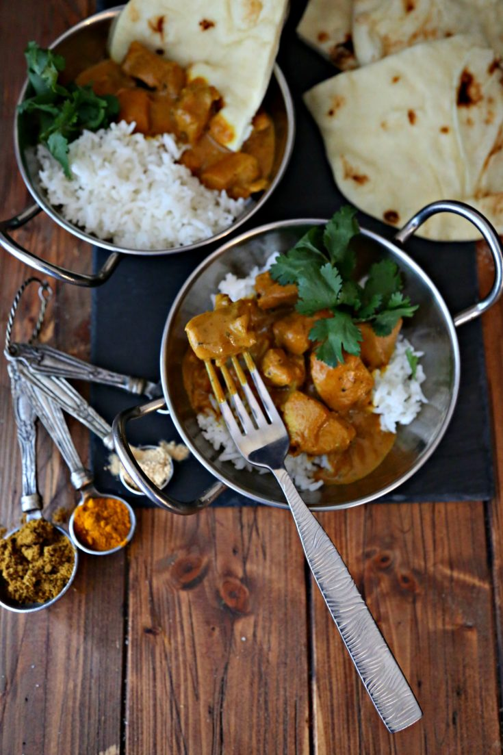 two bowls of Indian butter chicken with rice and naan bread. Measuring spoons filled with spices surrounding