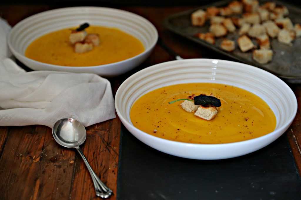 2 bowls of Roasted Butternut Squash Soup with spoons and a tray of toasted croutons