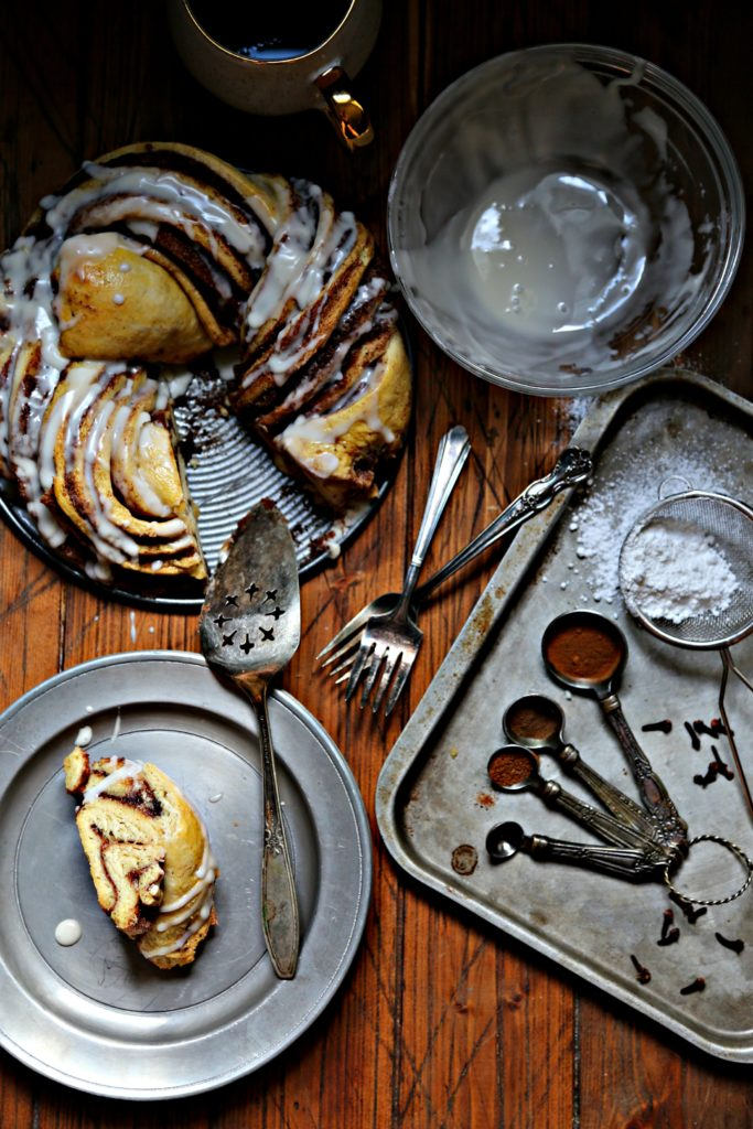 Pumpkin Spice Brioche with Maple Glaze, glass bowl of empty glaze, measuring spoons with spice on baking sheet, plate with slice of brioche