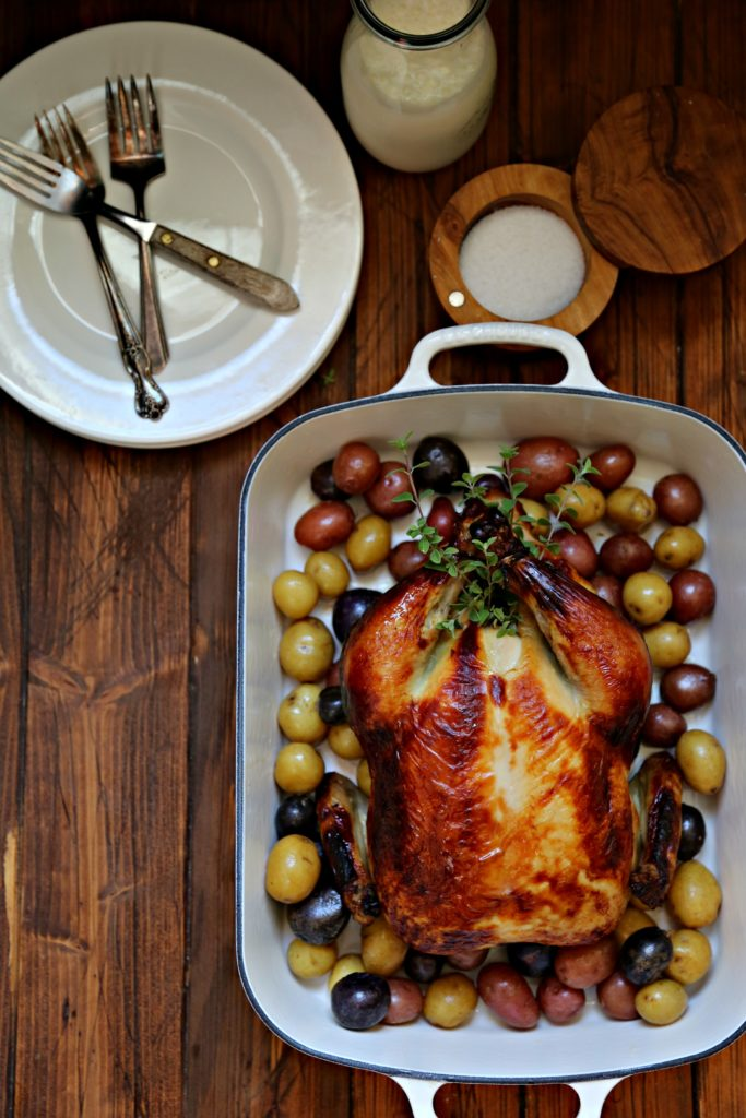 Buttermilk Brined Roast Chicken in roasting dish with new potatoes, salt cellar and white plates surrounding