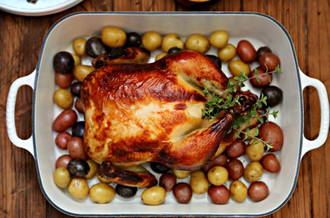 Buttermilk Brined Roast Chicken in roasting pan surrounded by new potatoes