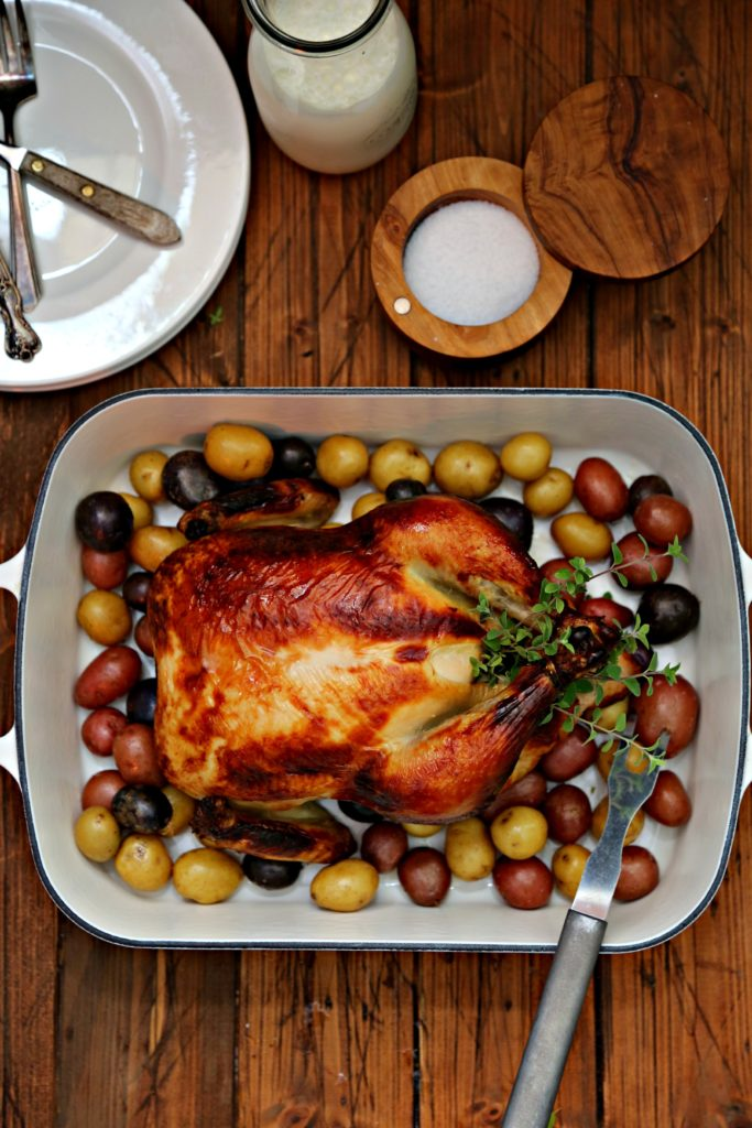 Buttermilk Brined Roast Chicken in roasting pan surrounded by new potatoes, salt cellar and white plates