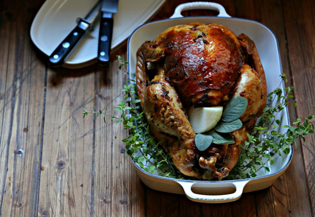 Mayonnaise Herb Roated Turkey in roaster with herbs, plate with carving utensils beside.