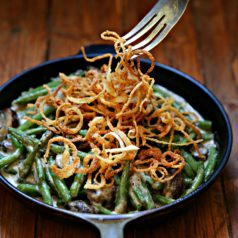 Fresh Green Bean Casserole in a skillet with Crispy Onions being pulled with fork