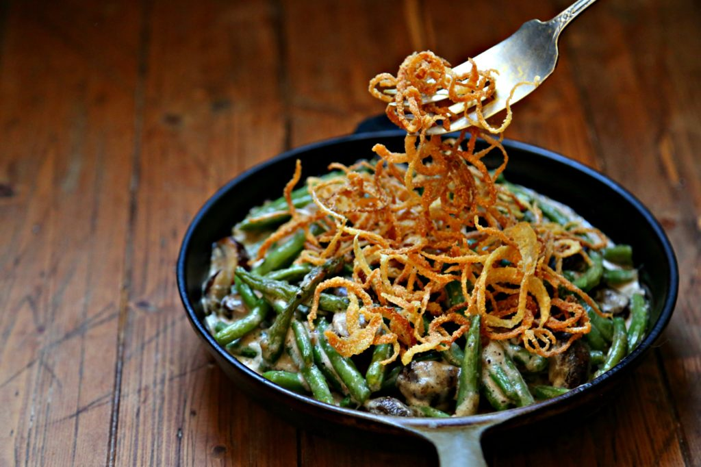 Fresh Green Bean Casserole with Crispy Onions in skillet with fork pulling onions