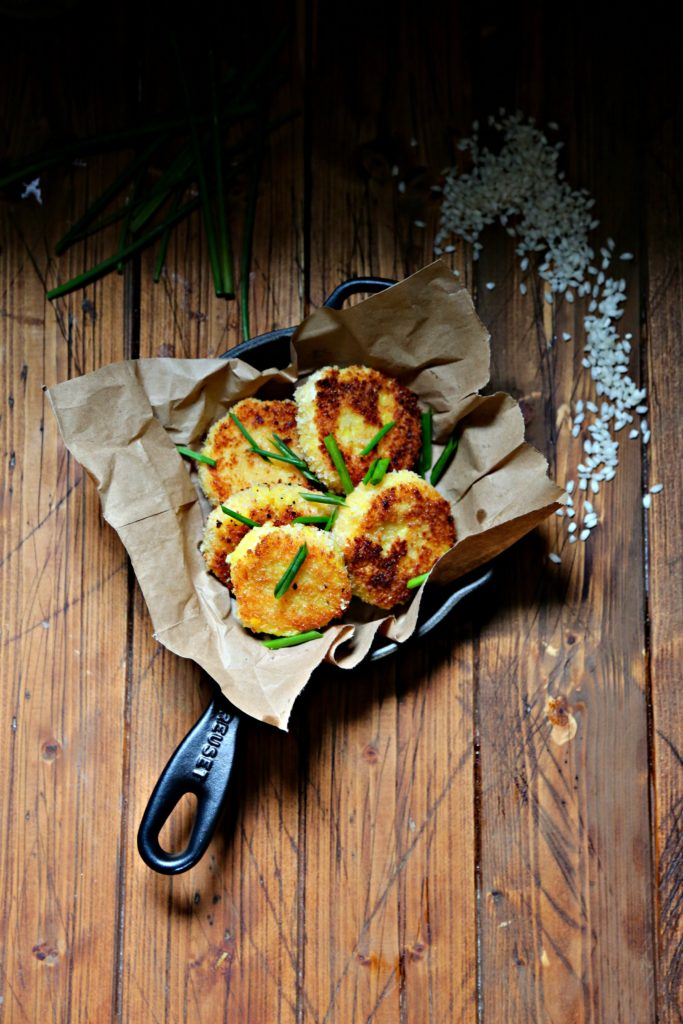 Saffron Risotto Cakes in skillet with risotto scattered to side
