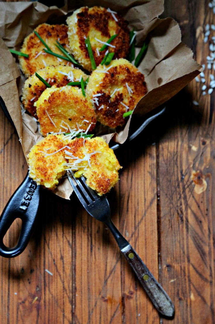 saffron risotto cakes inside black skillet with fork in one cake