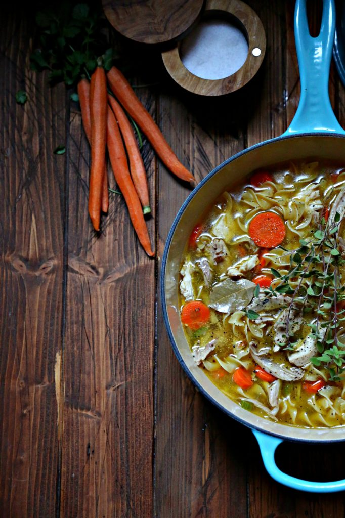 Quick and Easy Homemade Chicken Noodle Soup in a blue pot with carrots off to side