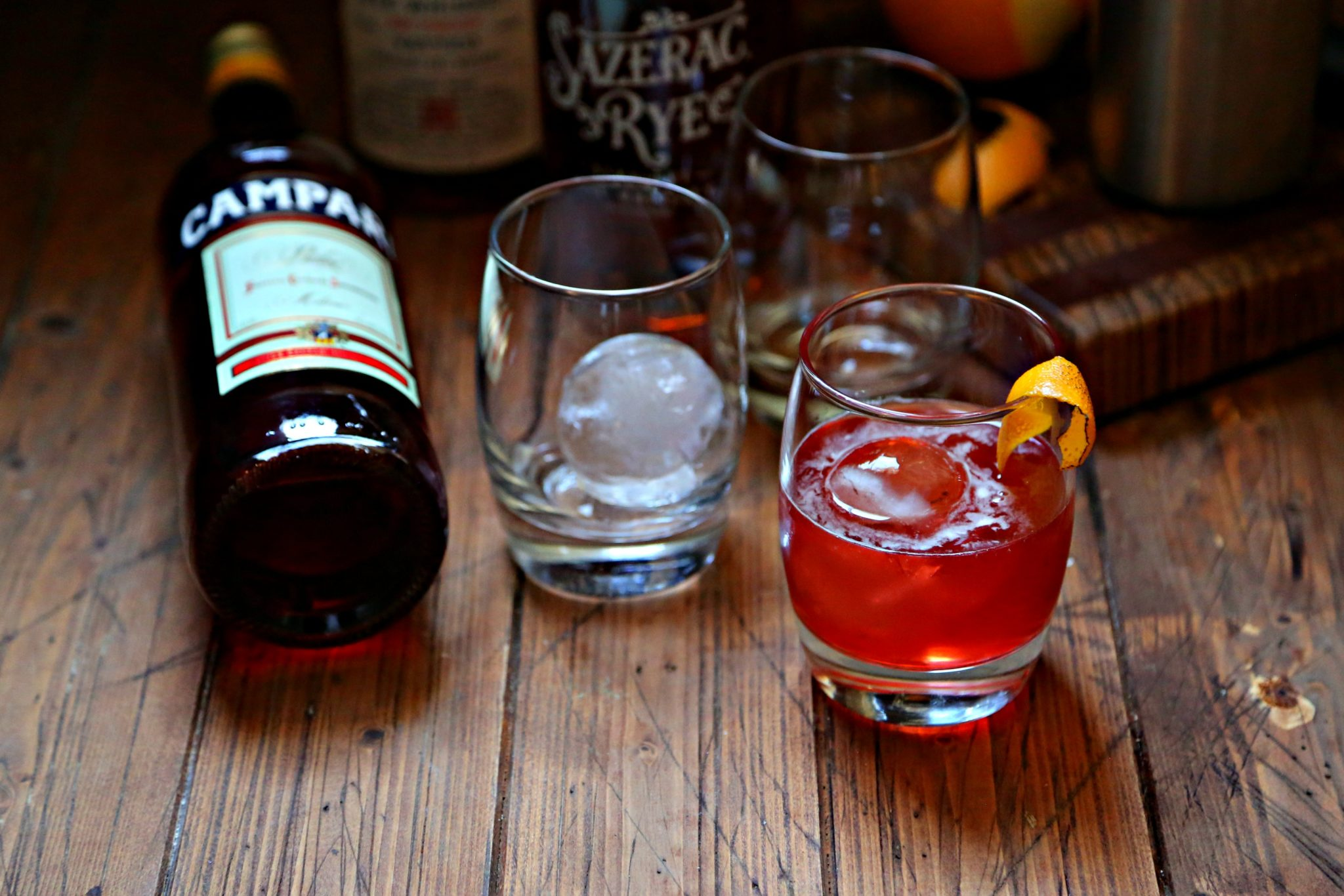 Boulevardier Cocktail with ice sphere and orange peel, extra glasses, bottle of campari and rye whiskey to side