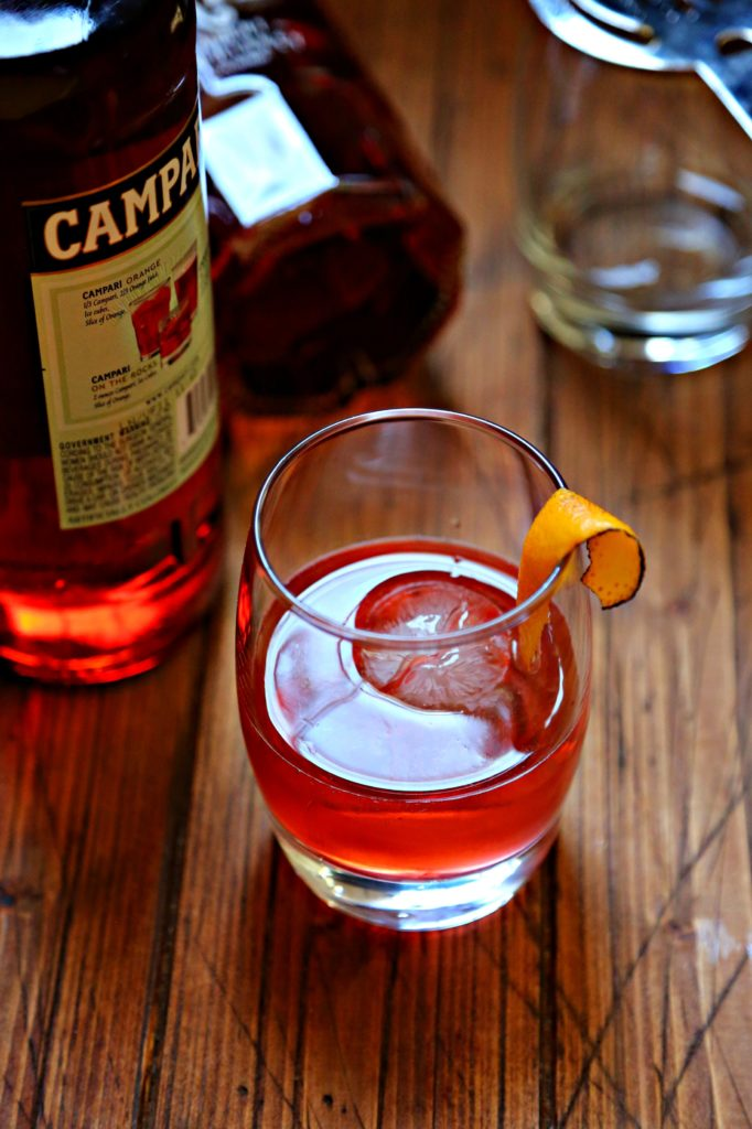 Boulevardier Cocktail with sphere ice cube and orange peel, campari bottle and rye whiskey bottle to side