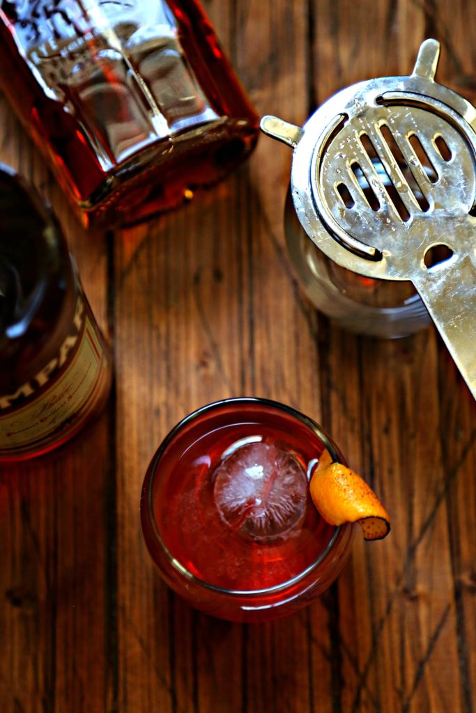 Boulevardier Cocktail with ice sphere and orange peel, campari bottle and rye whiskey bottle to side with strainer