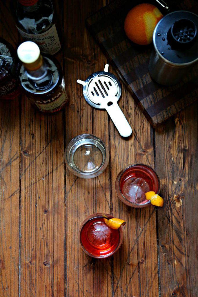 Boulevardier Cocktail with bottle of Camparie, extra glass with ice sphere and strainer to side