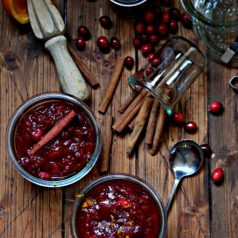 Cinnamon Orange Cranberry Sauce in glass jars surrounded by cinnamon sticks and fresh cranberries