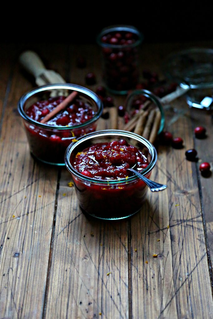 Cinnamon orange cranberry sauce in jars with cinnamon sticks to side