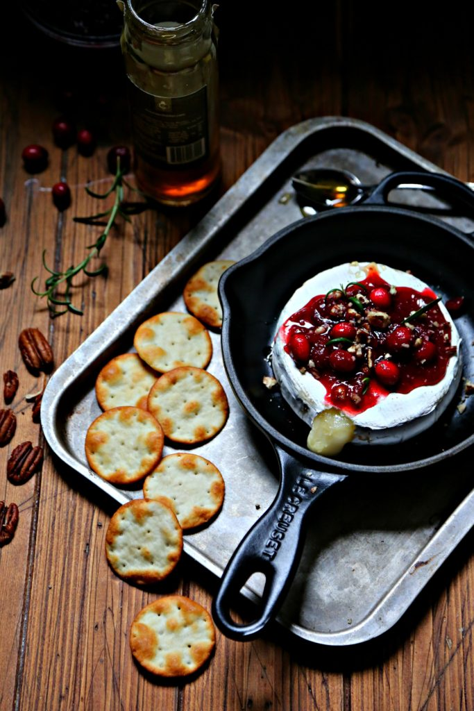 Cranberry Pecan Baked Brie in cast iron skillet surrounded by crackers