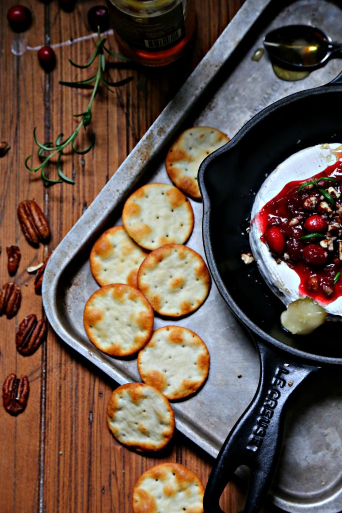Cranberry Pecan Baked Brie in skillet surrounded by crackers and pecans