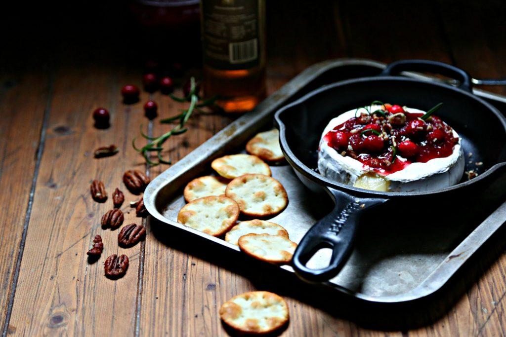 Cranberry Pecan Baked Brie in skillet surrounded by crackers