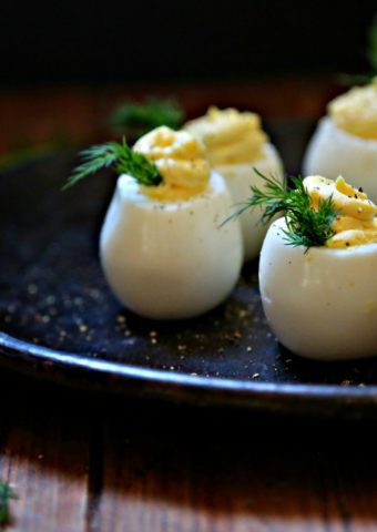 Deviled Eggs on brown plate garnished with dill