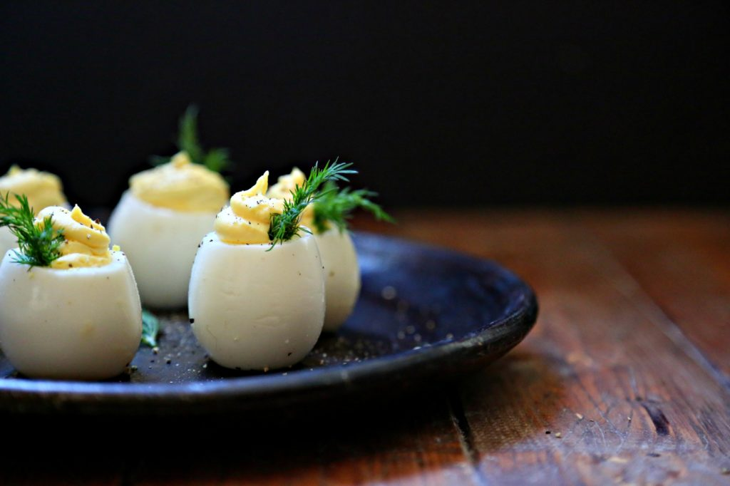 Deviled Eggs garnished with dill on brown plate