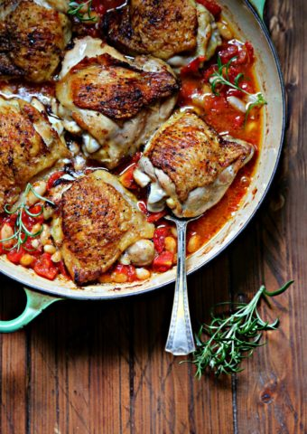 Skillet Chicken Thighs with Fire-Roasted Tomatoes and White Beans in green skillet with spoon and rosemary to side