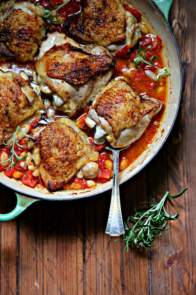 Skillet Chicken Thighs with Fire-Roasted Tomatoes and White Beans in green skillet with serving spoon. Rosemary sprig in front.