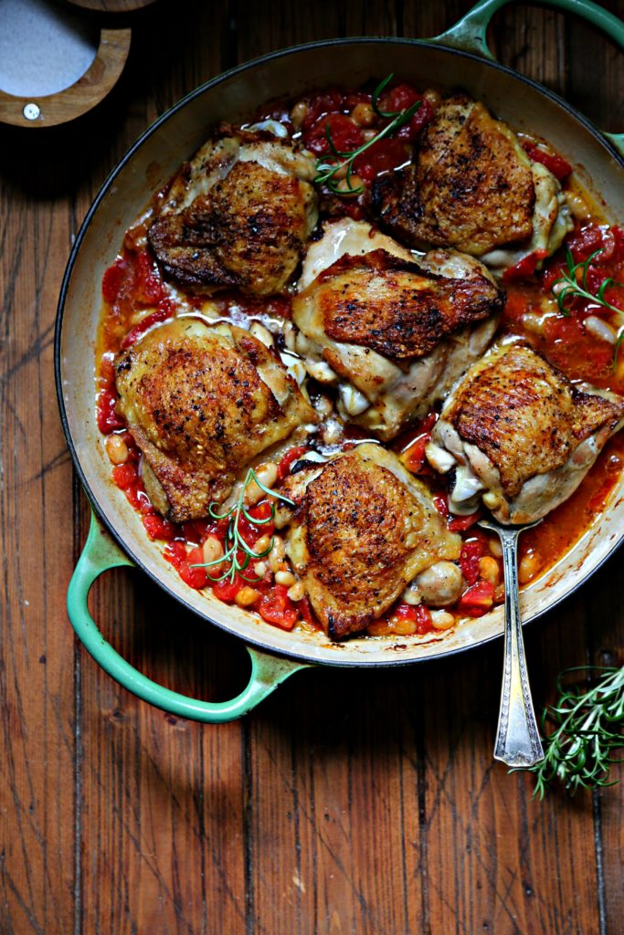 Skillet Chicken Thighs with Fire-Roasted Tomatoes and White Beans in green skilet with spoon and rosemary to side