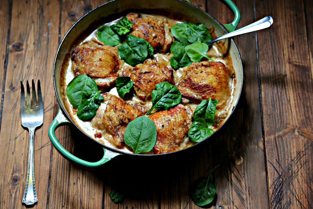 Chicken Thighs with Creamy Garlic Mushroom Sauce in green skillet with fork and spoon